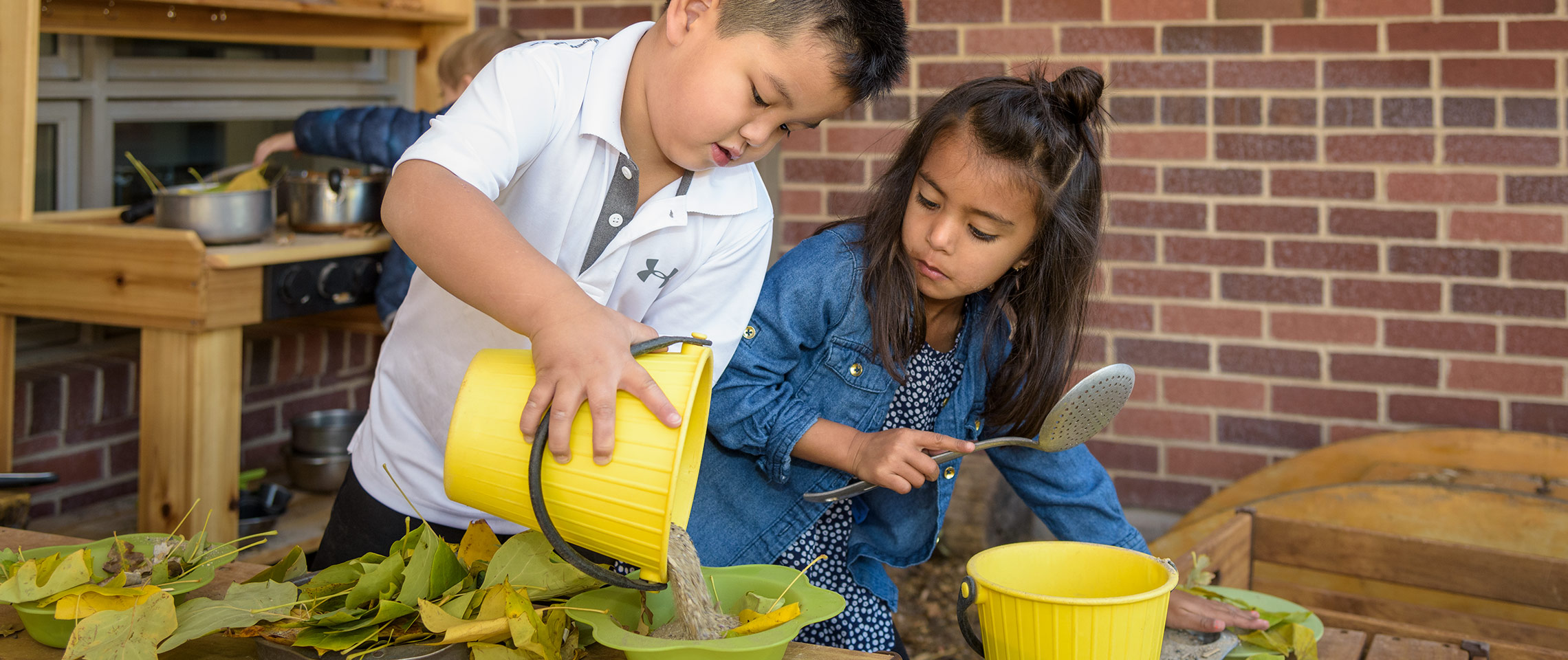 Beginning schoolers playing in the mud kitchen.